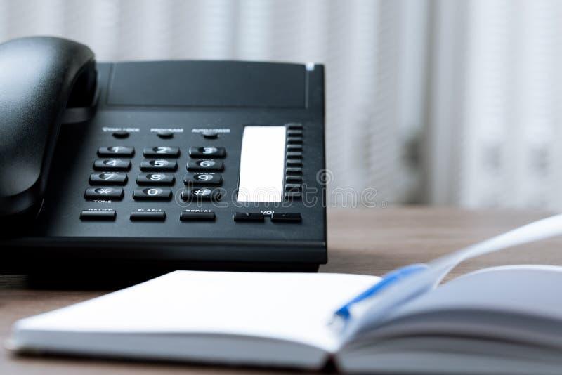 Mesa de escritório com telefone e agenda imagens de stock