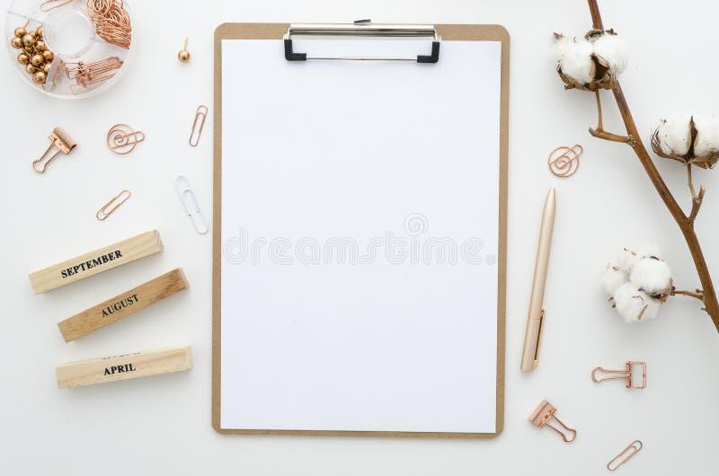 A mesa de escritório domiciliário do modelo com placa de grampo, braçadeiras de papel, pena dourada, algodão floresce em um fundo fotografia de stock royalty free