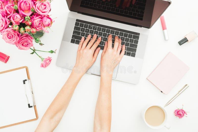Mesa de escritório domiciliário Espaço de trabalho com mãos fêmeas, portátil da mulher, ramalhete cor-de-rosa das rosas, acessóri imagem de stock