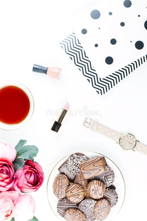Mesa de escritório domiciliário lisa da configuração Espaço de trabalho fêmea com almofada de nota, flores, chá, cookies do choco imagem de stock