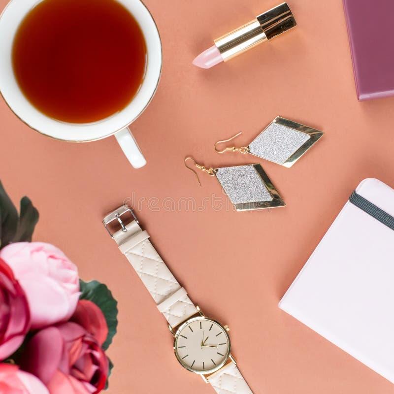 Mesa de escritório domiciliário lisa da configuração Espaço de trabalho fêmea com almofada de nota, flores, chá, cookies do choco fotos de stock