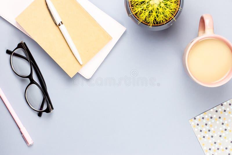 Mesa de escritório domiciliário lisa da configuração Espaço de trabalho fêmea com livro de nota, monóculos, caneca do chá, diário fotografia de stock