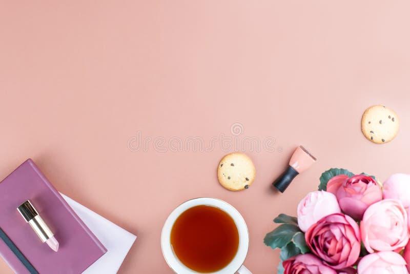 Mesa de escritório domiciliário lisa da configuração Espaço de trabalho feminino com diário, flores, doces, acessórios de forma C imagem de stock royalty free