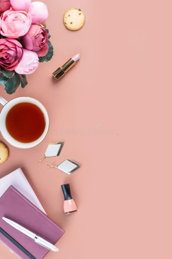 Mesa de escritório domiciliário lisa da configuração Espaço de trabalho feminino com diário, flores, doces, acessórios de forma C fotografia de stock royalty free