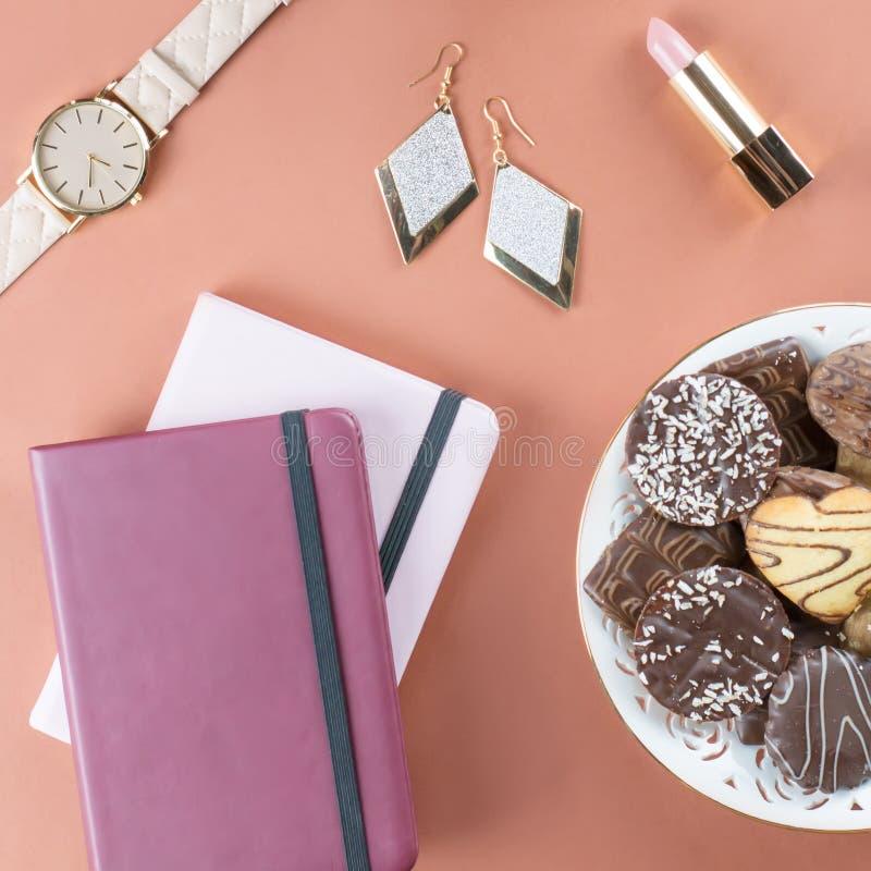 Mesa de escritório domiciliário lisa da configuração Espaço de trabalho feminino com diário, flores, doces, acessórios de forma C fotos de stock royalty free