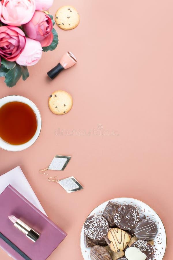 Mesa de escritório domiciliário lisa da configuração Espaço de trabalho feminino com diário, flores, doces, acessórios de forma C imagem de stock