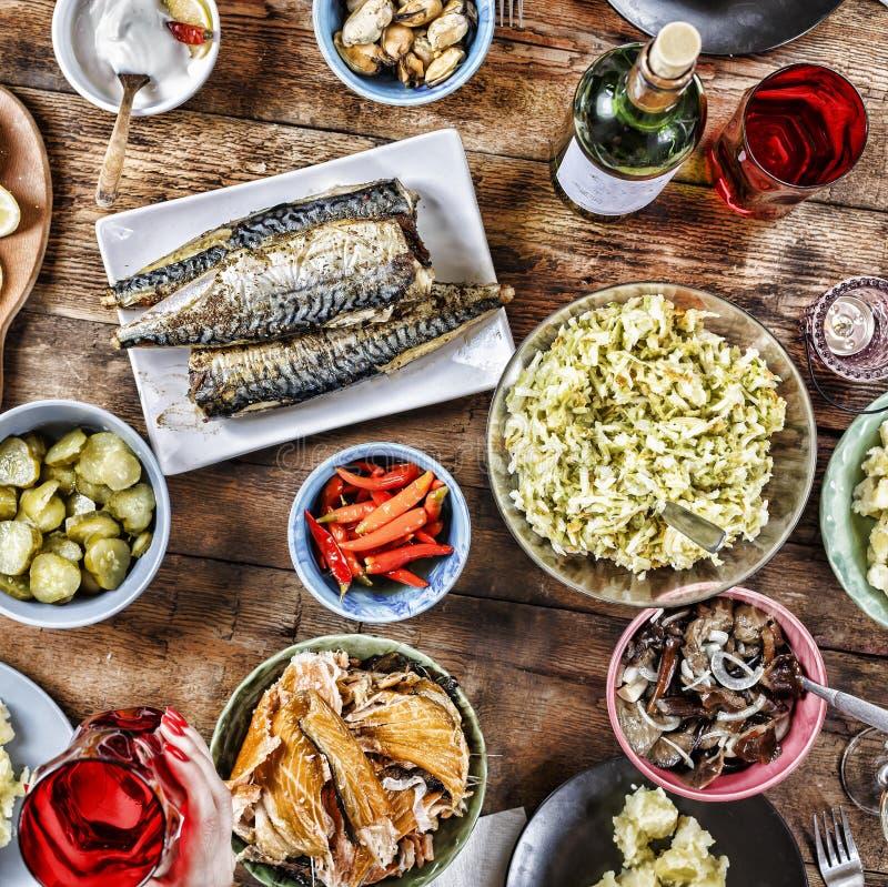 Mesa de jantar com uma variedade de petiscos e saladas Os salmões, azeitonas, vinho, vegetais, grelharam o brinde dos peixes o co fotografia de stock