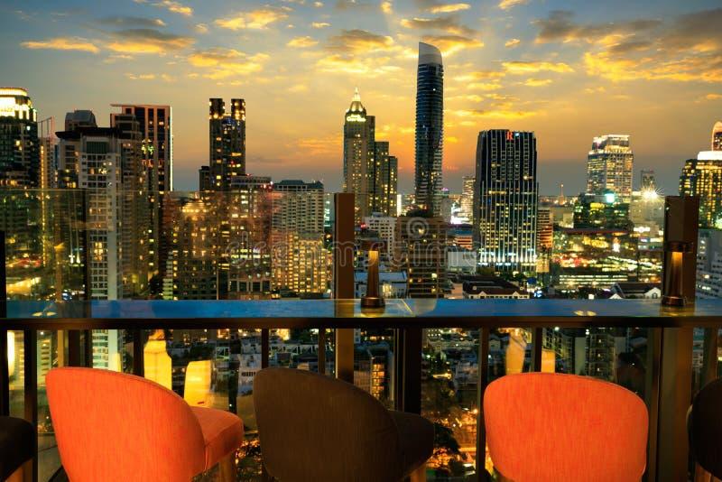Mesa de jantar do restaurante e vista da construção do negócio no terraço no crepúsculo fotos de stock royalty free