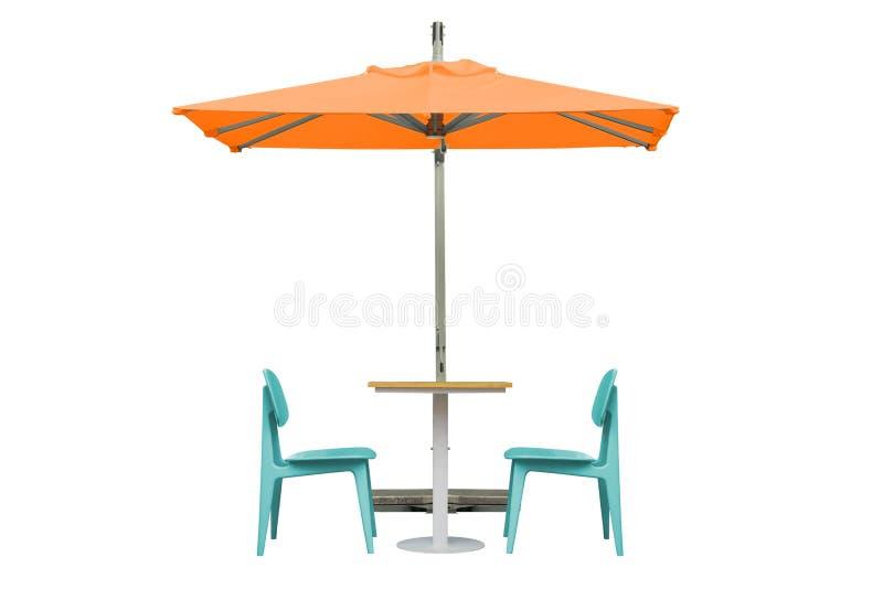 Mesa de jantar e cadeiras exteriores com o guarda-chuva alaranjado isolado no fundo branco imagens de stock