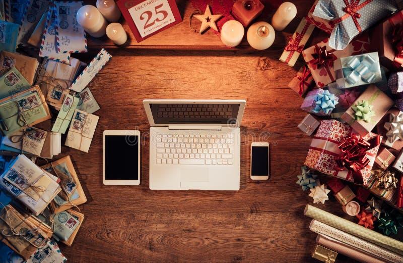 Mesa de la Navidad con el ordenador portátil y los dispositivos móviles imagen de archivo libre de regalías
