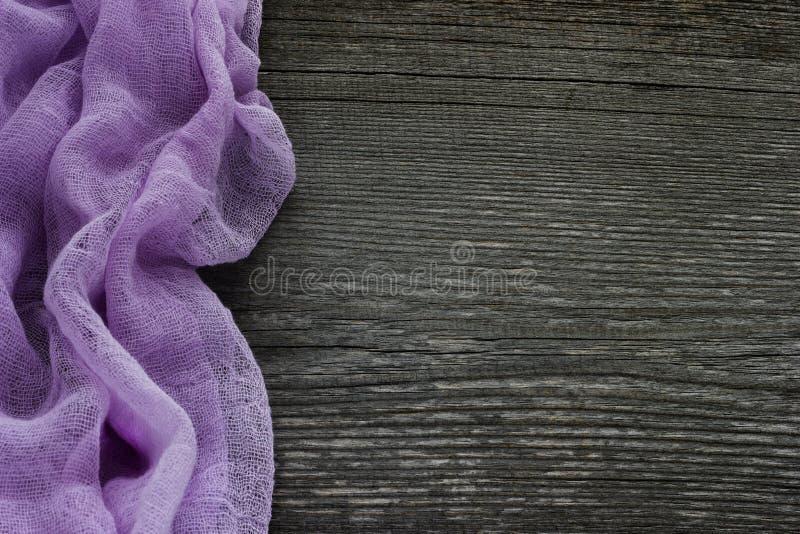 Mesa de madeira cinzenta velha com a matéria têxtil roxa bonita Fundo imagem de stock