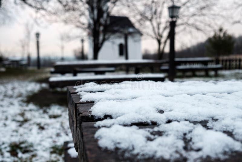 Mesa de madeira no jardim coberto pela neve, pelas lâmpadas e pela igreja pequena no fundo imagens de stock