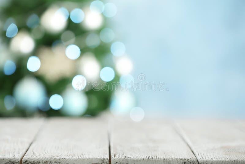 Mesa de madera blanca vacía y abeto borroso con luces de Navidad en segundo plano. Espacio para el diseño fotos de archivo libres de regalías