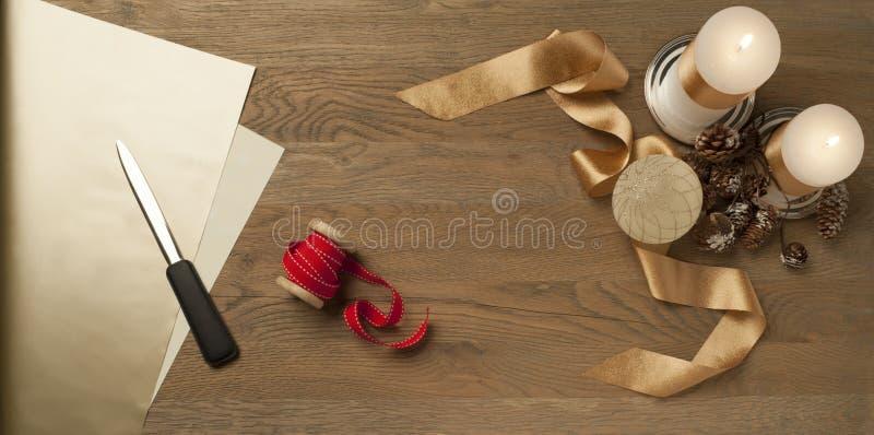 Mesa de madera de Navidad con cintas rojas y doradas y velas imagen de archivo