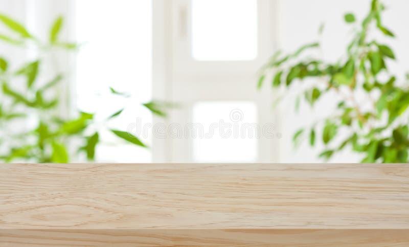 Mesa de madera sobre la ventana borrosa y fondo de plantas verdes fotos de archivo libres de regalías