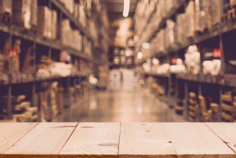 Mesa de madera vacía sobre cajas borrosas desenfocadas en filas de estanterías foto de archivo libre de regalías