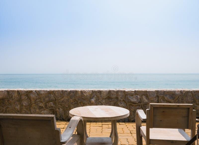 Mesa de madera y silla para relajarse al aire libre junto a la playa imagenes de archivo