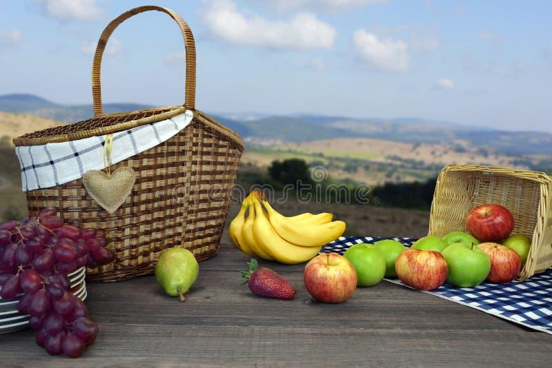 Mesa de picnic con dos cestas y frutas y paisajes de la montaña fotos de archivo
