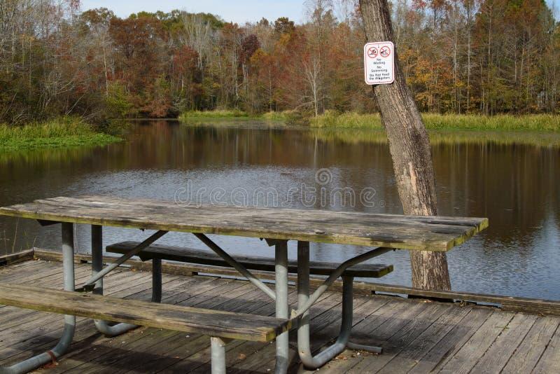 Mesa de picnic con la señal de peligro del cocodrilo imágenes de archivo libres de regalías