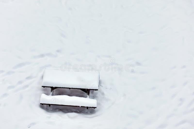 Mesa de picnic del banco de madera en un parque cubierto con nieve fotos de archivo