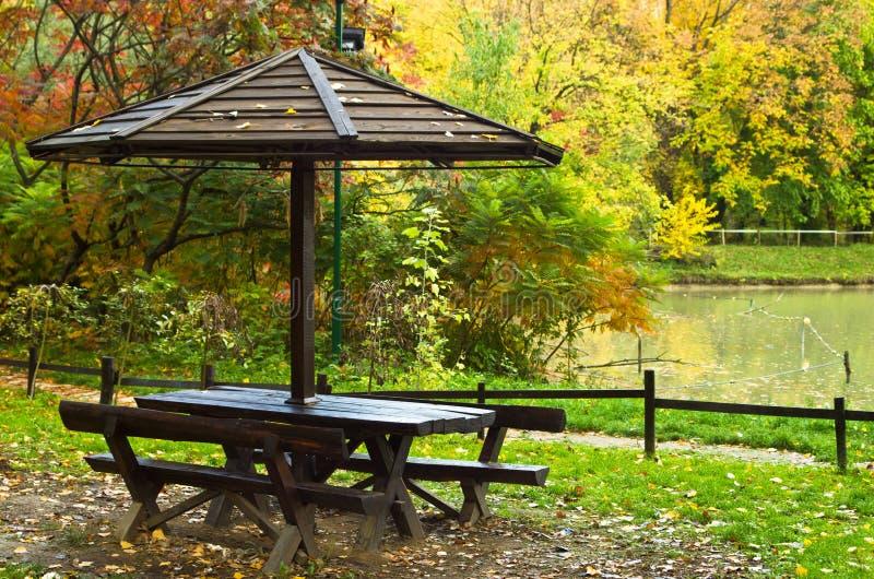 Mesa de picnic por el lago rodeado por el bosque en colores del otoño imagen de archivo libre de regalías