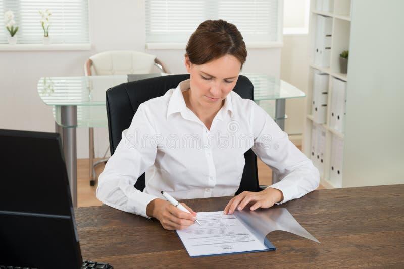 Mesa de Reading Document At da mulher de negócios fotografia de stock