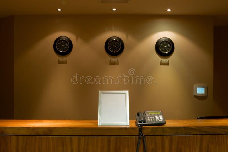 Mesa de recepção do hotel com telefone e quadro indicador fotos de stock