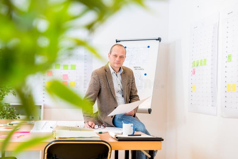 Mesa de reuniones orgullosa de Holding Blueprint On del hombre de negocios imagenes de archivo