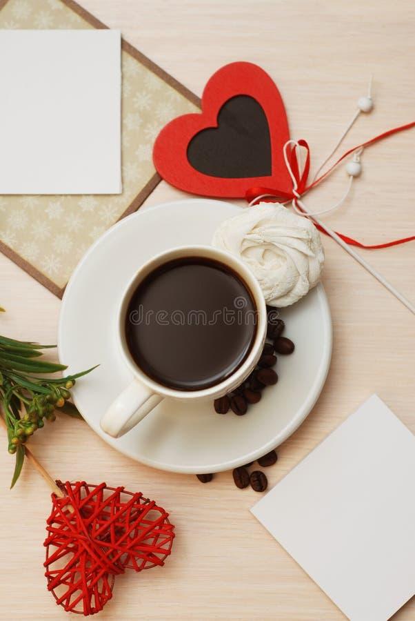 Mesa de trabajo con el ordenador portátil, taza de café, hojas del verde Forma del corazón, amor Fondo neutral beige Concepto de  foto de archivo
