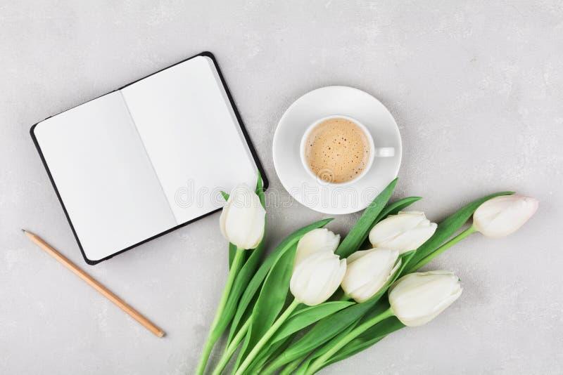 A mesa de trabalho da mulher com caneca de café, caderno e tulipa da mola floresce a vista superior no estilo da configuração do  imagens de stock