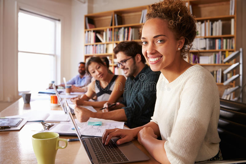 Mesa de Using Laptop At da mulher de negócios no escritório ocupado fotografia de stock