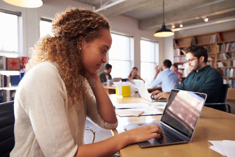 Mesa de Using Laptop At da mulher de negócios no escritório ocupado imagem de stock