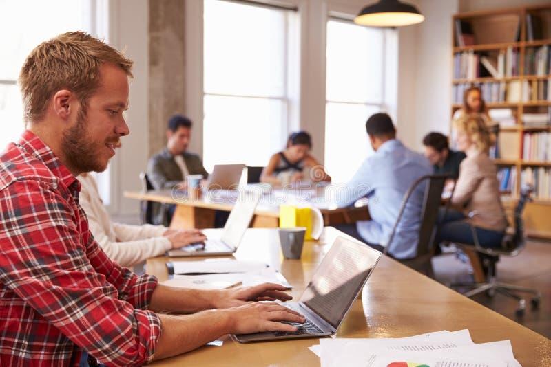 Mesa de Using Laptop At do homem de negócios no escritório ocupado foto de stock