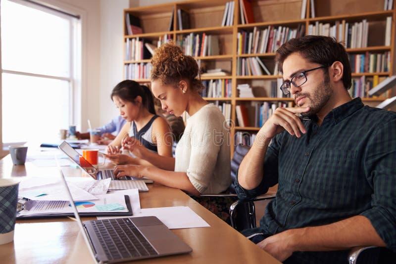 Mesa de Using Laptop At do homem de negócios no escritório ocupado imagens de stock