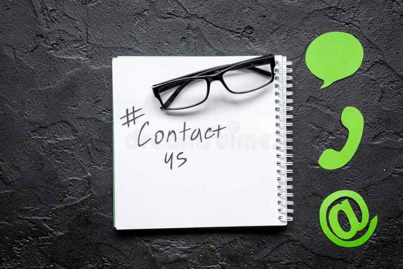 Mesa del servicio de atención al cliente con el contacto nosotros muestras en la opinión superior del fondo oscuro imágenes de archivo libres de regalías