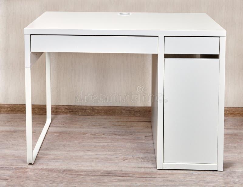 Mesa do computador com as duas gavetas perto da parede imagem de stock