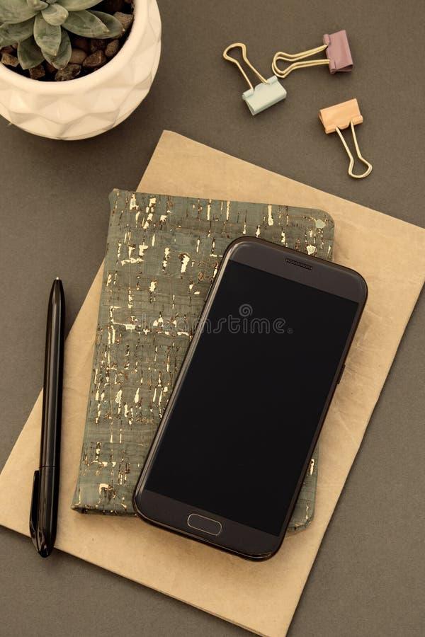 Mesa do espa?o de trabalho Configura??o lisa, estilo minimalistic moderno, com caderno, smartphone, planta suculento foto de stock