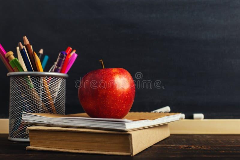 A mesa do professor com materiais de escrita, um livro e uma maçã, uma placa para o texto ou um fundo para um tema da escola Copi imagens de stock