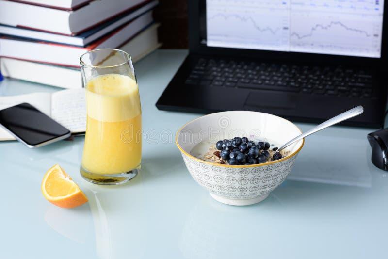 Mesa en oficina de la bolsa de acción con el desayuno y el ordenador portátil que muestran la carta del mercado de acción imágenes de archivo libres de regalías