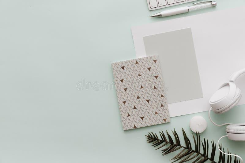 Mesa minimalista del inconformista de la endecha del plano Fondo en colores pastel del Blogger con el cuaderno foto de archivo