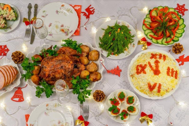 Mesa navideña festiva con deliciosa comida y objetos decorativos Cena para Año Nuevo, pavo de Navidad Invierno fotos de archivo