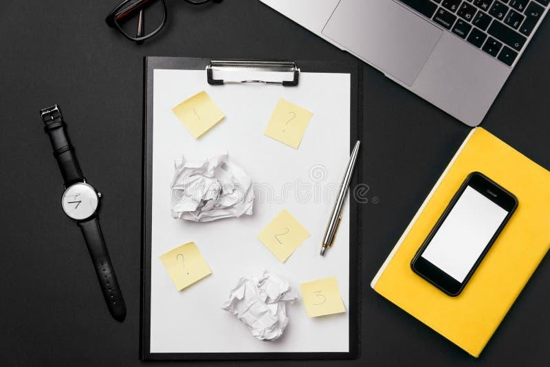Mesa negra de la oficina con la hoja de papel blanca con el espacio y pluma de la copia libre, ordenador port?til, vidrios, reloj foto de archivo libre de regalías
