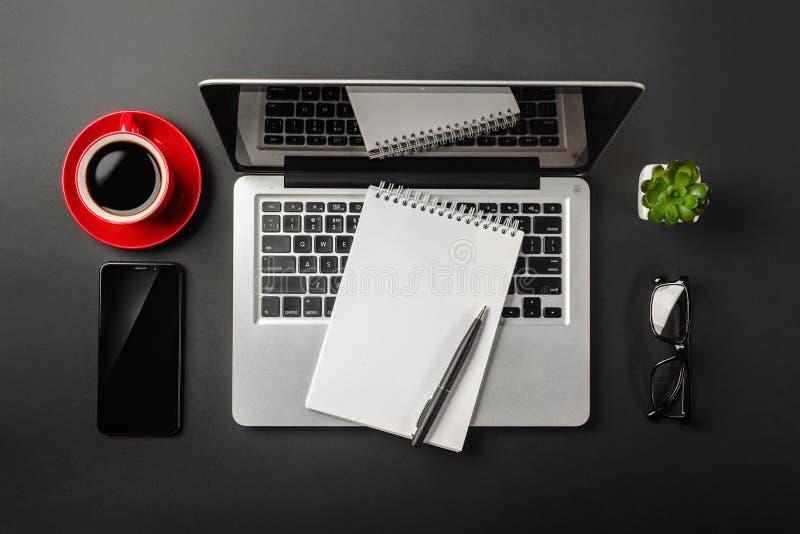 Mesa negra elegante de la oficina con el ordenador portátil, el cuaderno, la taza de café roja y el teléfono móvil imagen de archivo