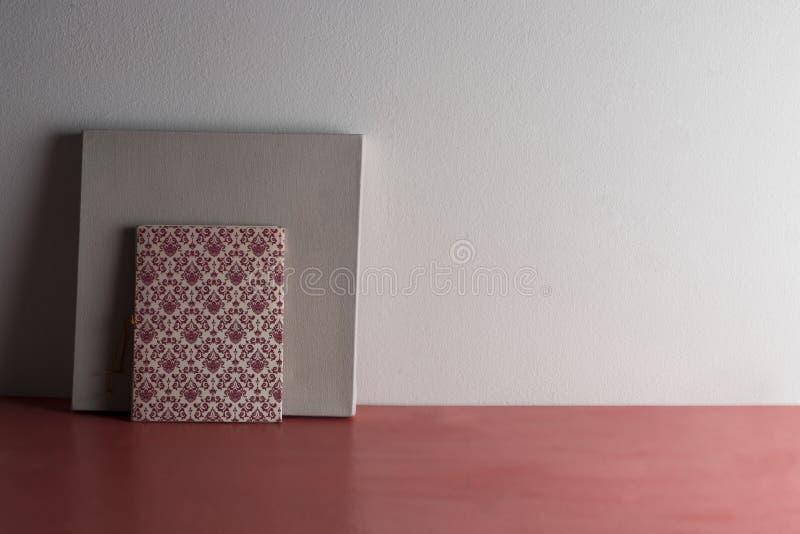 Mesa no coral vivo com caderno e lona vazia imagem de stock royalty free