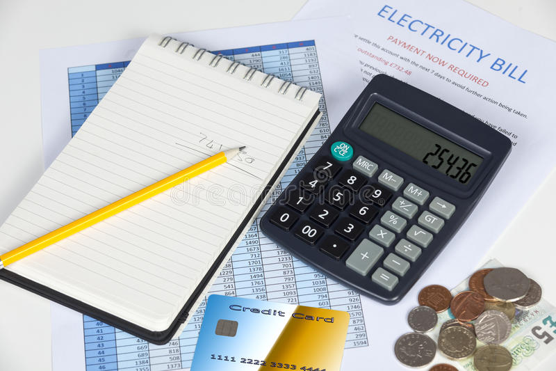 Mesa que muestra una cuenta vencida de la electricidad con una calculadora y una tarjeta de crédito fotografía de archivo libre de regalías