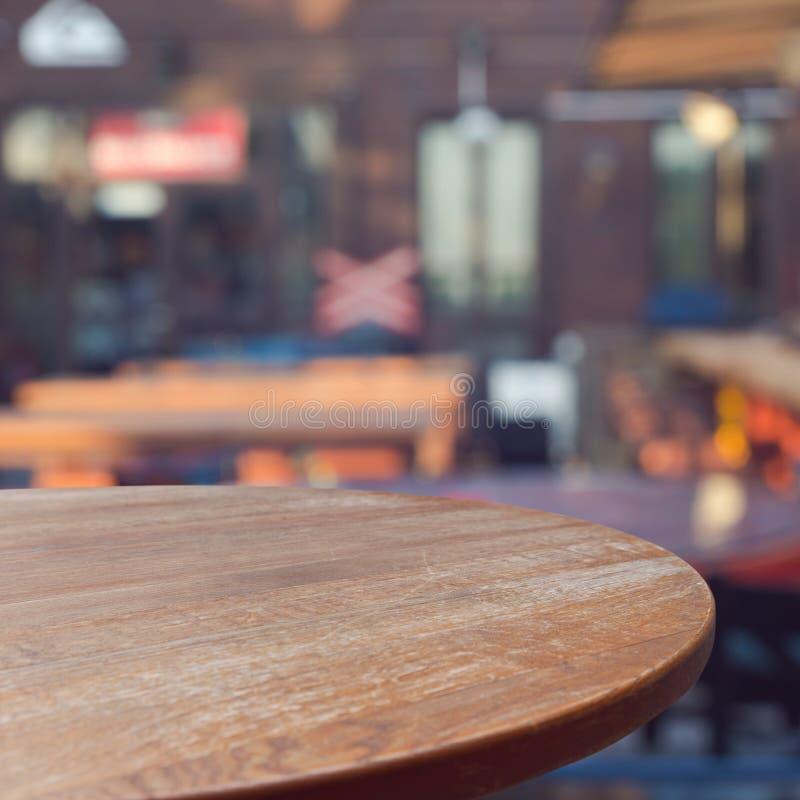 Mesa redonda de madera vacía sobre fondo al aire libre del restaurante foto de archivo