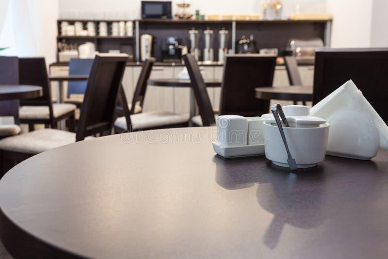 Mesa redonda e açucareiro de madeira, guardanapo, sal e pimenta no café moderno com mobília da cozinha no fundo imagens de stock
