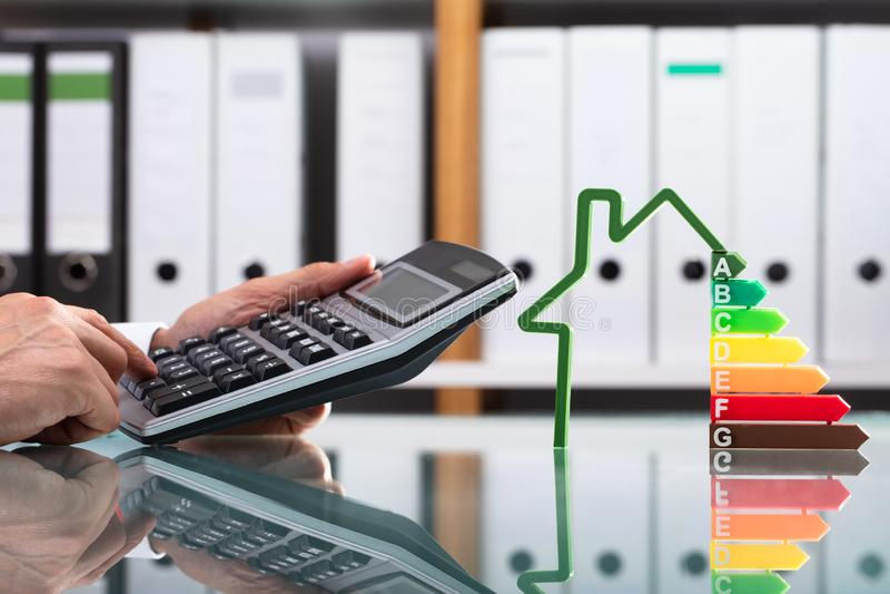 Mesa reflexiva de Using Calculator Over do homem de negócios imagem de stock royalty free