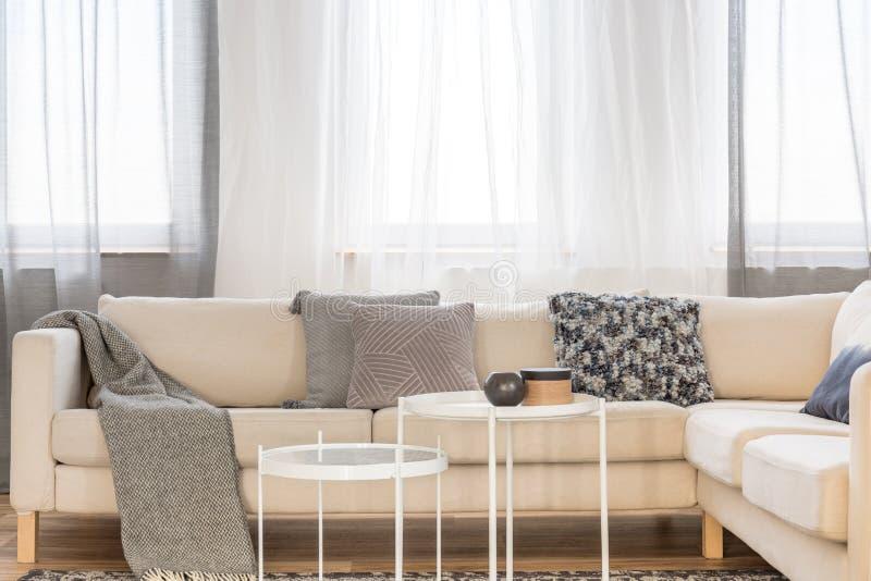 Mesas de centro industriales blancas en la sala de estar brillante interior con el sofá de la esquina grande imagen de archivo libre de regalías