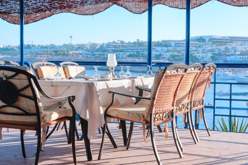 Mesas de comedor del restaurante que pasan por alto una bahía en un turista tropical foto de archivo
